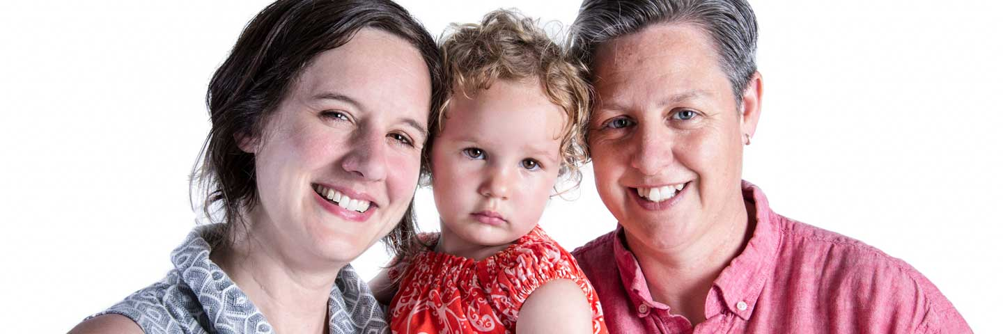 Two mothers hold toddler daughter.